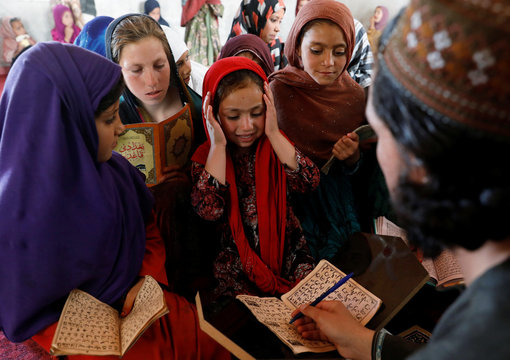 An Internally displaced Afghan girl reacts as she reads the Koran at a mosque, amidst the spread of the coronavirus disease (COVID-19) during the holy fasting month of Ramadan, in Kabul