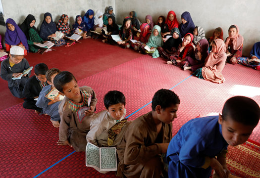 Internally displaced Afghan children read the Koran at a mosque, amidst the spread of the coronavirus disease (COVID-19) during the holy fasting month of Ramadan, in Kabul