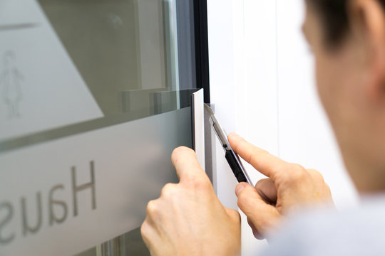 Signmaker cuts adhesive film on the window