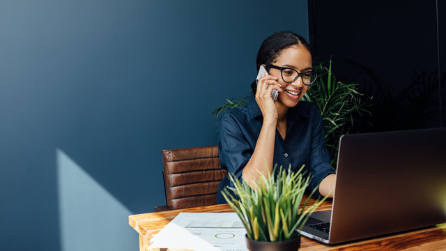 Entrepreneur sitting at table typing on a laptop while talking on cell phone