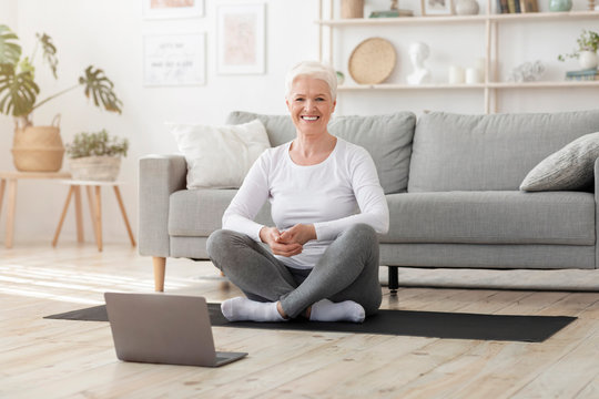 Online training. Calm senior woman practicing yoga at home with laptop, meditating and doing breathing exercise, empty space