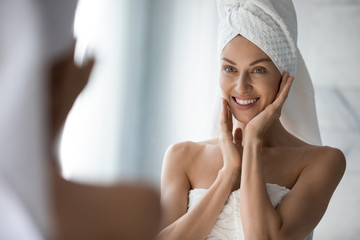 Foto op Plexiglas Spa After shower body and head wrapped in towel 35s woman looks in mirror touches moisturized soft healthy face skin feels satisfied enjoy spa cosmetics treatment procedure, morning care hygiene concept