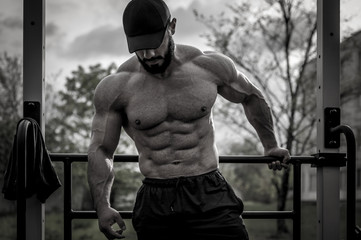 handsome young sport athlete bearded man in cap during outdoor gym body fitness workout training...