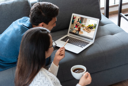 Couple staying at home attending course online together learning new skills about healthy food
