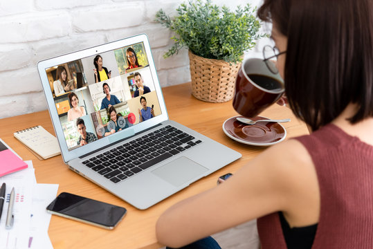 Woman use laptop with screen of video conference meeting  with 9 other people, work from home comceptual
