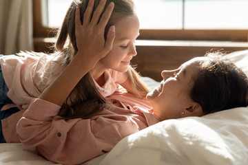 Happy mother and adorable little daughter lying in comfortable bed together, enjoying tender...