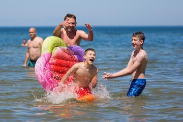 Fototapeta Zabawa w morzu, roześmiana rodzina chlapie się wodą, chłopiec spada z kolorowego materaca obraz