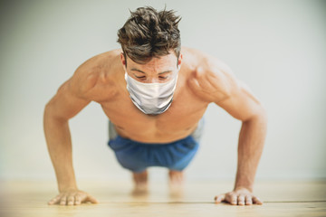 young man doing push ups in fitness studio with flu mask