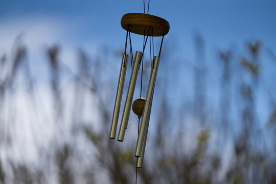 Wind Chimes blowing in the summer air. Natural background. Windy day. Melodic music with tubes. Bright blue sky. Estonia, Baltic, Europe