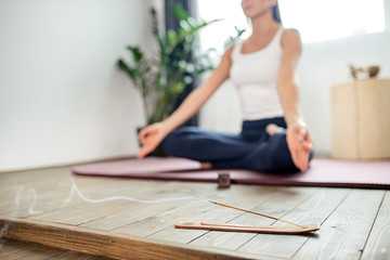 cropped photo of woman meditating in lotus position on turquoise yoga mat on the floor. Focus on incense stick and smoke. Relax after yoga training, healthy lifestyle concept