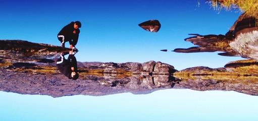 Reflection Of Man Sitting On Headland Fotobehang