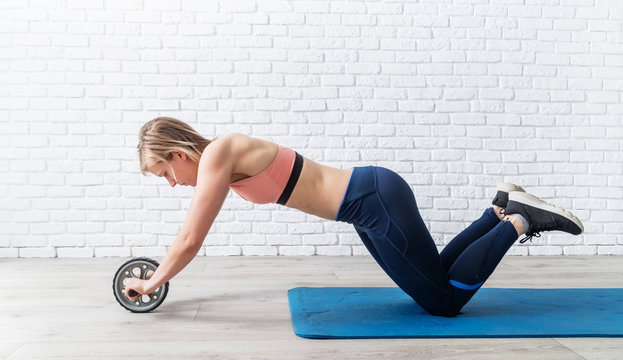 woman doing abdominal exercises with gymnastic roller