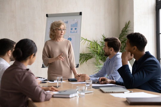 Confident mature 60 year old businesswoman presentation new project in boardroom at company meeting. Adult woman coach auditor speaks about business on flip chart graphs background.