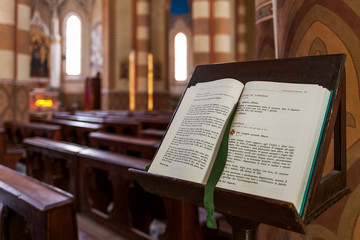 Open Bible on the stand inside San Lorenzo Cathedral (aka Duomo) in Alba, Italy.