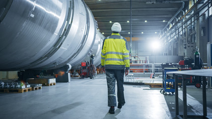 Shot of Heavy Industry Engineer Walking through Pipe Manufacturing Factory. Modern Facility for Design and Construction of Large Diameter Oil, Gas and Fuels Transport Pipeline.