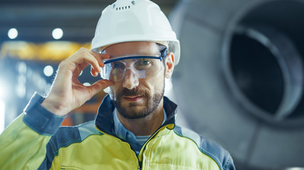 Portrait of Smiling Professional Heavy Industry Engineer / Worker Wearing Safety Uniform and Hard Hat Putting on Glasses. In the Background Unfocused Large Industrial Factory
