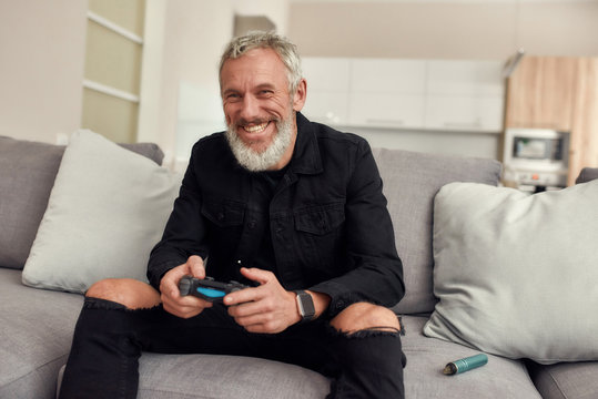 Relax. Happy bearded middle-aged man holding controller, playing video games, sitting on the couch at home. Weed vaporizer, dry herb vape pen lying next to him. Cannabis and weed legalization concept