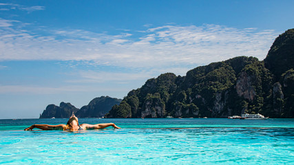 pretty woman relaxing in infinity pool, looking at sea view and enjoying vacations.