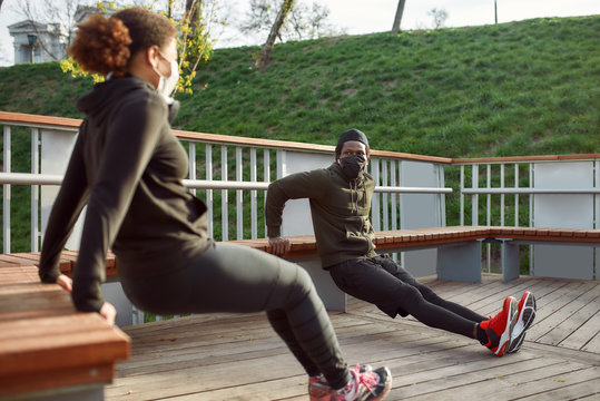 Social distancing. African couple in protective masks working out in park outdoors. Doing push-ups exercises on bench, training triceps