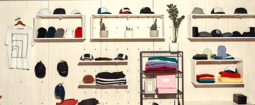 Limitless solutions. Custom apparel, clothes neatly arranged or folded on shelves. Stack of colorful clothing and baseball caps in the store