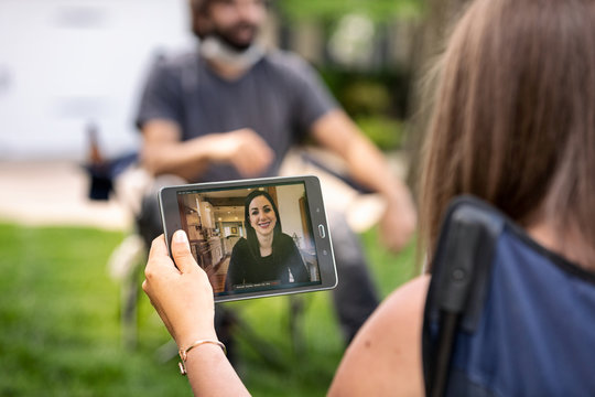 Distanced: Woman Talking To Friend On Digital Tablet Who Stayed Home