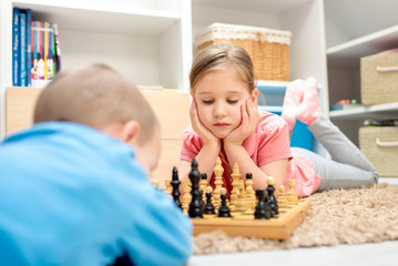 Little girl playing chess at home with her little brother