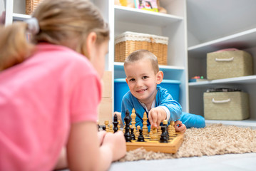 Children having fun while playing chess at home