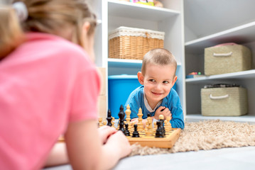 Little boy playing chess with his sister and having fun together