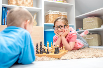 Adorable little girl playing chess with her brother in the kids room