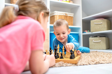 Brother and sister playing chess and having fun together