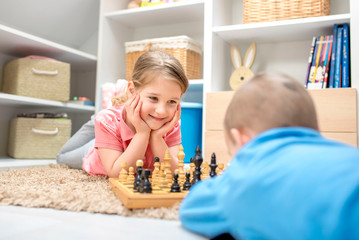Little girl playing chess with her brother and having fun together