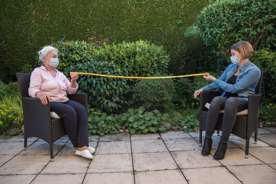 Senior woman and caregiver with protective masks measuring safety distance
