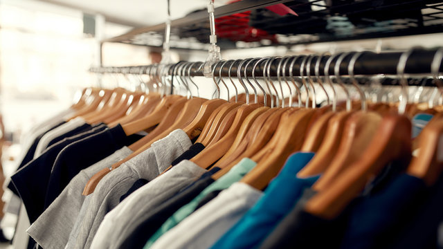 Wide range. Close up of clothes rack or rail in the store. Items at custom T-shirt, clothing printing company