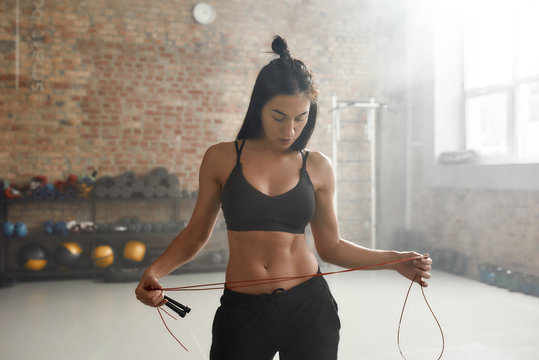 Move your body, shape your future. Sportive woman in black sportswear holding jump rope while having workout at industrial gym