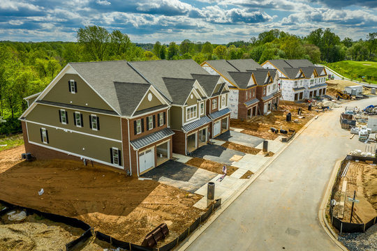Elevated view of almost finished luxury townhouses with two single car garages, brick and shake and shingle siding, gable roof with attic vent on a new residential development in Maryland USA