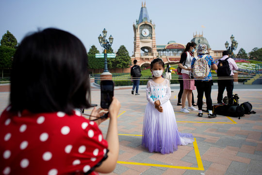 A girl wearing face mask poses for a picture at Shanghai Disney Resort as the Shanghai Disneyland theme park reopens following a shutdown due to the coronavirus disease (COVID-19) outbreak, in Shanghai