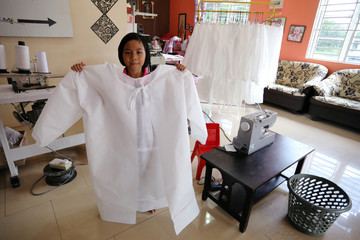Nur Afia Qistina Zamzuri, a 9-year-old girl poses for a picture holding a personal protective equipment (PPE) she made for free to medical workers working in local hospitals at her home, amid the coronavirus disease (COVID-19) outbreak, in Kuala Pilah