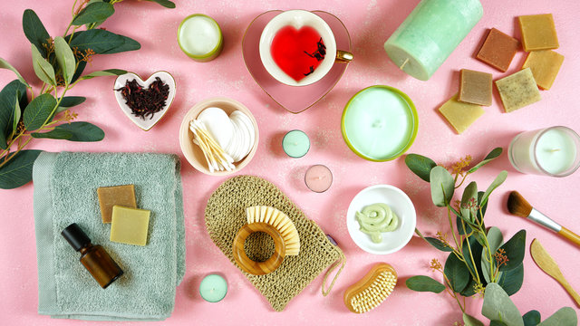 Self-care wellbeing home spa creative concept flatlay with herbal hibiscus tea, pro environmental plastic free beauty products and moisturisers on feminine pink background.