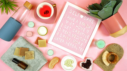 Self-care wellbeing home spa letterboard with herbal hibiscus tea, pro environmental plastic free beauty products and moisturisers on feminine pink background.