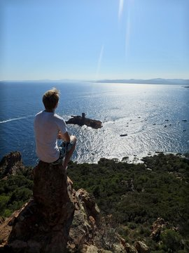 Rear View Of Young Man Sitting On Cliff And Looking At View