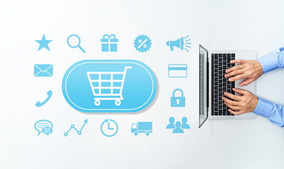 Online shop and e-commerce concept. Top view of using laptop. Many blue e-commerce icons.