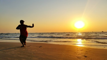 Full Length Of Man Performing Martial Arts On Beach During Sunset