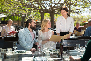Waitress helping visitors with menu on outdoor terrace