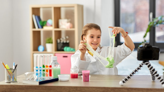 science, childhood and blogging concept - happy smiling little girl blogger with slime and camera on tripod recording video blog at home laboratory