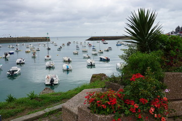boats in the harbor framed by old stone jettys and coloful flower pots along the edge of the sea in Brittany, France