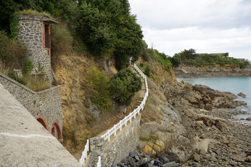 old stone path with white fence along the edge of the rocky  coast of Brittany, France
