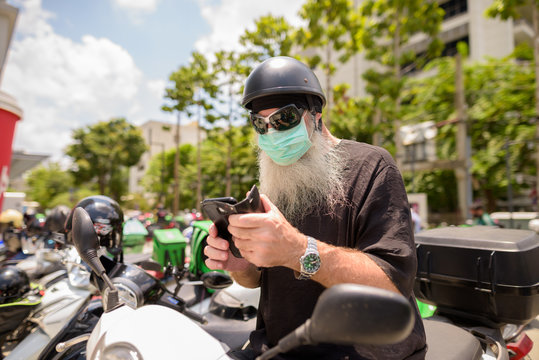 Mature bearded hipster man with sunglasses and mask using phone while sitting on motorcycle