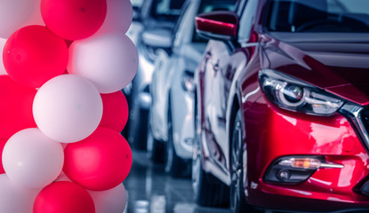 Red and white balloons decorated in modern car showroom on blurred of front view red SUV car. New and shiny luxury SUV car parked in modern showroom. Car dealership office. Automotive industry.