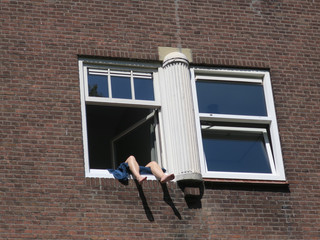staying inside during corona: sunning with legs hanging out of the window