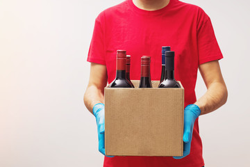 Courier wearing protective gloves holding box with bottles of wine.